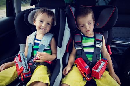 asiento coche: Dos niños dulces, dormir en el coche con los osos de peluche después de un largo viaje