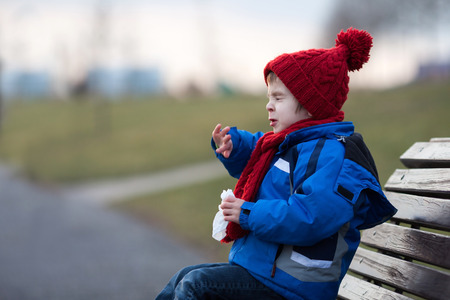 Little boy, sneezing and blowing his nose outdoor on a sunny winter day, sitting on a bench Stock Photo