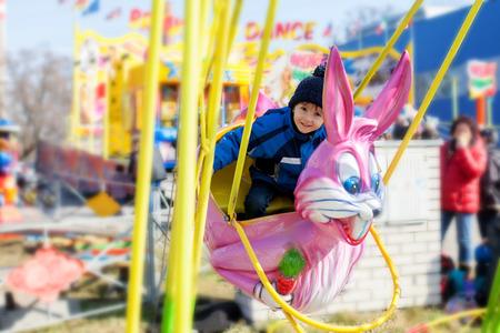 pink rabbit: Adorable little boy, swinging on a pink rabbit in amusement park Stock Photo