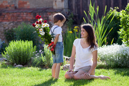 Beautiful kid and mom in spring park, flower and present. Mothers day celebration concept Standard-Bild
