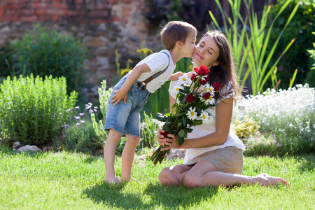 Beautiful kid and mom in spring park, flower and present. Mothers day celebration concept Foto de archivo