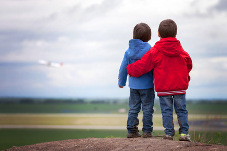 Adorable boys in read and blue jackets, stanging on a hill, watching airplane taking off