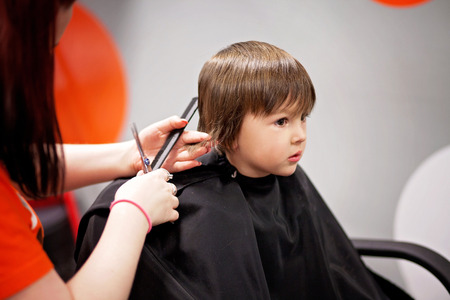 barber background: Cute little boy, having haircut in barber shop Stock Photo