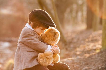 oso de peluche: Adorable ni�o con su amigo el oso de peluche en el parque en la puesta del sol, luz de fondo agradable Foto de archivo