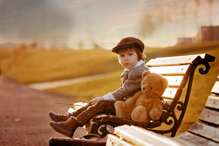 back light: Adorable little boy with his teddy bear friend in the park on sunset, nice back light