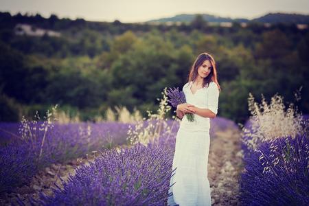flor de lavanda: Joven y bella mujer, la celebraci�n de la lavanda en un campo en la puesta del sol Foto de archivo