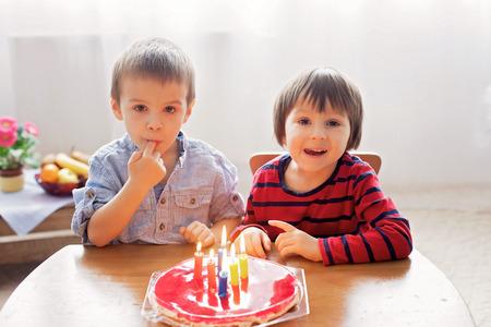 Entzückende süße Jungs, bläst Kerzen auf einem Geburtstagskuchen zu Hause Standard-Bild - 38669400