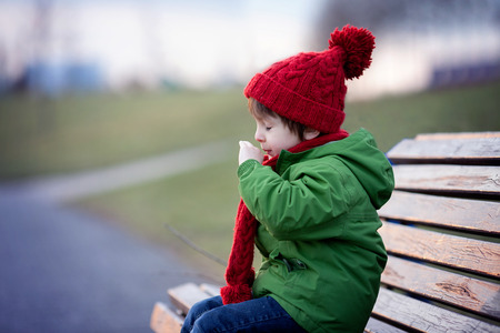 flu: Little boy, sneezing and blowing his nose outdoor on a sunny winter day, sitting on a bench Stock Photo