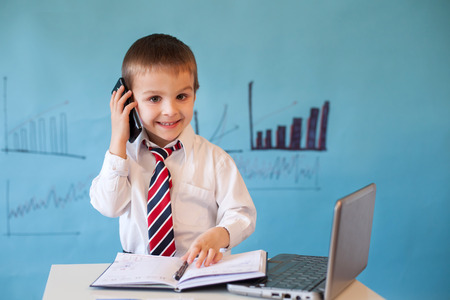 Smart little boy, working on computer, taking notes and speaking on the phone Stock Photo