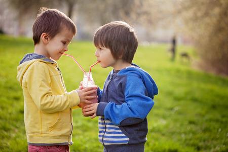 licuado de platano: Muchachos dulces en el parque, sosteniendo la botella con batido, beber y sonriente, primavera Foto de archivo