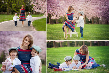 Beautiful portrait of mother and her two children in a cherry blossom tree garden, waking down the alley, holding hands and looking at the camera photo