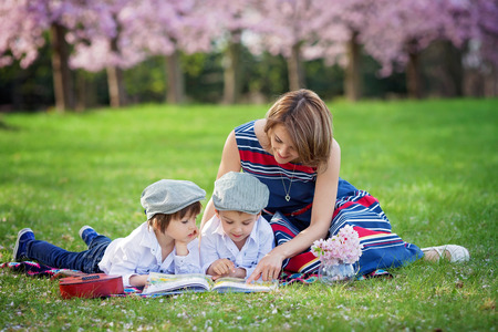 Beautiful portrait of two adorable caucasian boys and their mom, reading a book in a cherry tree blooming garden, spring afternoon, kids lying on the grass on a blanket, vase with flowers and guitar