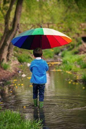 niños caminando: Niño pequeño lindo, caminando en un estanque en un día lluvioso, jugando y saltando, sonriendo, primavera