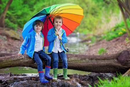 cute guy: Two adorable little boy, brothers, sitting on a wooden trunk on a pond in a rainy day with colorful umbrella, boots and casual clothing, smiling at the camera