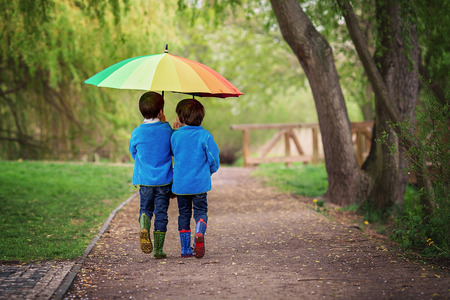 rainbow umbrella: Two adorable little boys, walking in a park on a rainy day, playing and jumping, smiling, talking together, springtime