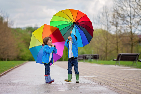 Two adorable little boys, walking in a park on a rainy day, playing and jumping, smiling, talking together, springtime