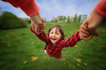girotondo bambini: Madre, spinning in cerchio il suo piccolo neonato, gioia pura, sfocatura radiale, primavera, giorno