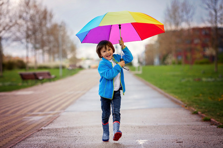 rainbow umbrella: Cute little boy, walking in a park on a rainy day, playing and jumping, smiling, springtime