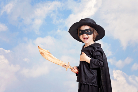 pretend: Superhero child with sward and costume on a blue sky background, smiling at the camera Stock Photo