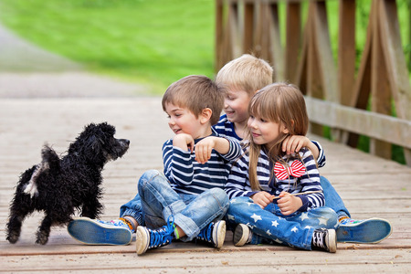 Three beautiful adorable kids, siblings, playing with cute little dog in the park, springtime