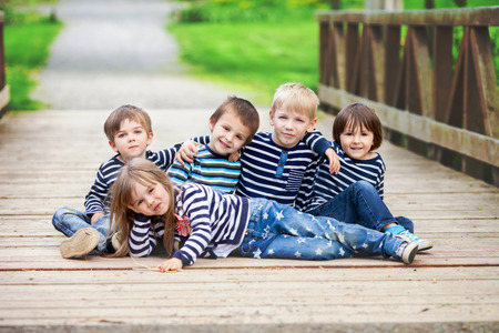 Five adorable kids, dressed in striped shirts, hugging and smiling, sitting on the grass in a dandelion field