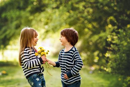 美しい男の子と女の子に公園、少年少女に花をあげます。友情の概念