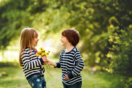 boys and girls: Beautiful boy and girl in a park, boy giving flowers to the girl. Friendship concept