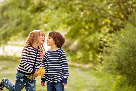 ��beautiful boy�: Beautiful boy and girl in a park, boy giving flowers to the girl. Friendship concept