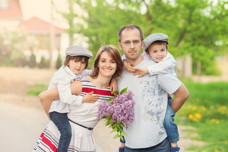 flowers boy: Family of four, mother, father and two boys, parent having the kids on piggy back, laughing, smiling, hugging, giving a kiss, holding flowers