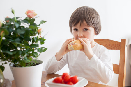 kids meal: Beautiful little boy, eating sandwich at home, vegetables on the table, back light Stock Photo