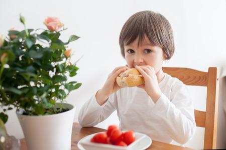 niños sanos: Niño pequeño hermoso, comiendo sándwich en casa, verduras en la mesa, luz de fondo Foto de archivo