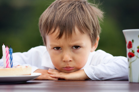 angry: Close-up portrait of angry little boy with a cake and tea, outdoor Stock Photo