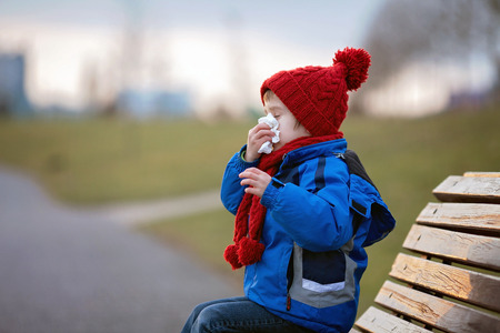 Little boy, sneezing and blowing his nose outdoor on a sunny winter day, sitting on a bench Standard-Bild