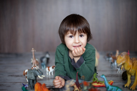 make believe: Beautiful little boy, smiling at camera, animals and dinosaurs around him, indoor shot