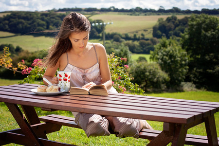 scones: Young attractive woman, reading a book outdoor, enjoying coffee and sweet scones with jam