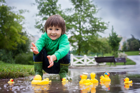 Little boy, jumping and playing in muddy puddles in the park, rubber ducks in the puddle