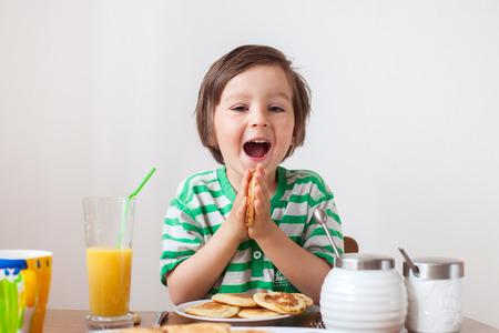 niños desayunando: Pequeño muchacho caucásico dulce, comer panqueques y beber jugo de naranja en el país Foto de archivo
