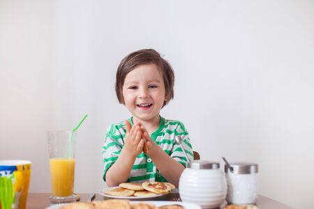 Sweet little caucasian boy, eating pancakes and drinking orange juice at home photo