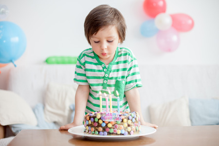and four of the year: Beautiful adorable four year old boy in green shirt, celebrating his birthday, blowing candles on homemade baked cake, indoor. Birthday party for kids Stock Photo