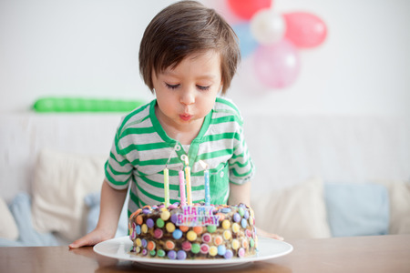 birthday presents: Beautiful adorable four year old boy in green shirt, celebrating his birthday, blowing candles on homemade baked cake, indoor. Birthday party for kids Stock Photo