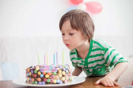 kids birthday party: Beautiful adorable four year old boy in green shirt, celebrating his birthday, blowing candles on homemade baked cake, indoor. Birthday party for kids Stock Photo