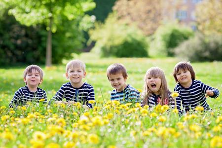 amicizia: Cinque bambini adorabili, vestite di camicie a righe per abbracciare e sorridente, seduto sull'erba in un campo di tarassaco. concetto di amicizia