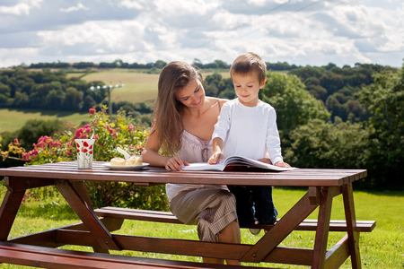 scones: Mother and son, reading a book outdoor, summer day, eating sweet scones