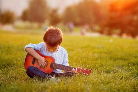 Schattige jongen met gitaar, zittend op het gras op zonsondergang Stockfoto