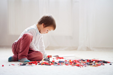 imagining: Little child playing with lots of colorful plastic blocks indoor, building a fire truck and a fire house, reading from a manual and imagining