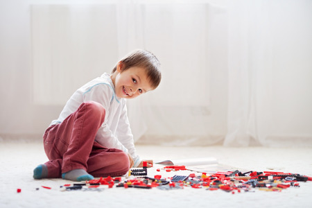 block: Little child playing with lots of colorful plastic blocks indoor, building a fire truck and a fire house, reading from a manual and imagining