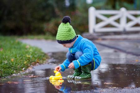 Niño pequeño, saltar en los charcos fangosos en el parque, patos de goma en el charco