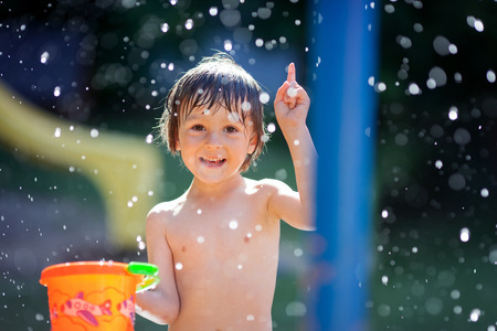 Cute little toddler boy, having fun with splashed water shot during summer time, holding bucket, outdoors