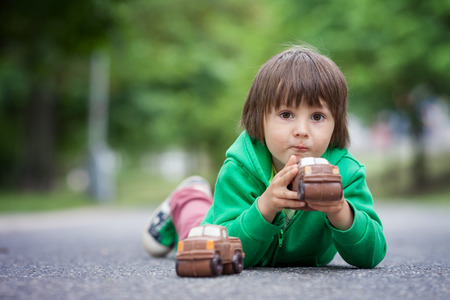 smudgy: Funny little boy playing with car of chocolate, outdoor, having fun