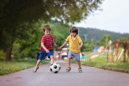 Two cute little kids, playing football together, summertime. Children playing soccer outdoor Stok Fotoğraf